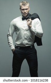 Male fashion, beauty concept. Portrait of brutal young man with short wet blond hair wearing black suit, posing over gray background. Classic style. Studio shot