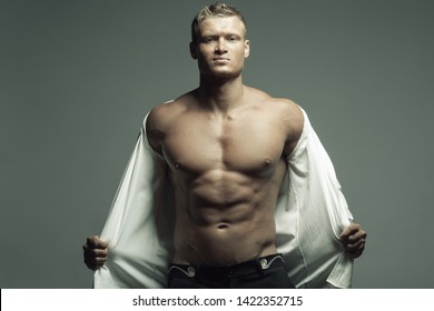 Male fashion, beauty concept. Portrait of brutal young man with short wet blond hair wearing white shirt, posing over gray background. Classic style. Text space. Studio shot