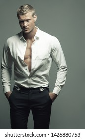Male fashion, beauty concept. Portrait of brutal young man with short wet blond hair wearing white shirt, black pants, posing over gray background. Classic style. Studio shot