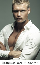Male fashion, beauty concept. Portrait of brutal young man with short wet blond hair wearing white shirt, posing over gray background. Classic style. Close up. Hands crossed. Studio shot
