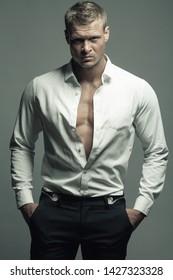 Männliche Mode, Schönheitskonzept. Portrait von brutalem jungen Mann mit kurzen nassen blonden Haaren mit weißem Hemd, schwarze Hose, posiert auf grauem Hintergrund. Klassischer Stil. Studioaufnahme