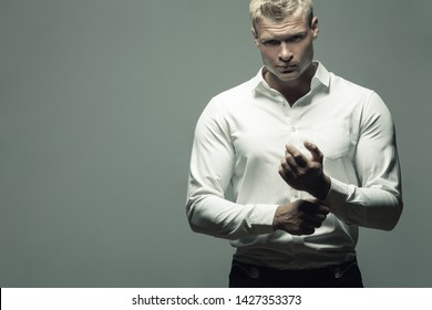 Male fashion, beauty concept. Portrait of brutal young man with short wet blond hair wearing white shirt, posing over gray background. Classic style. Copy-space. Studio shot