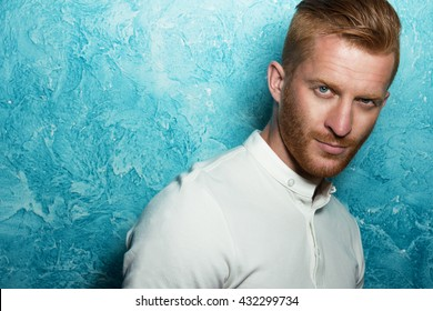 Male fashion concept. Portrait of young and handsome red(ginger) man posing over blue background. Close up. Studio shot