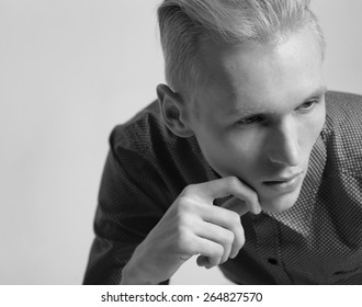 Male fashion model with blonde hair style against gray background in studio in black and white