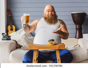 Male fatso drinking beer at home