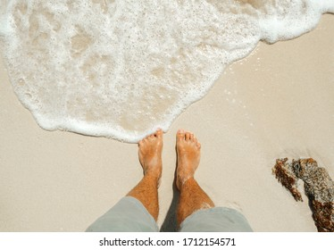 Male feet barefoot stand on the sand of the beach with sea foam. Tropical travel and vacation concept.
