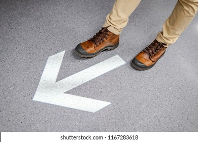 Male feet with casual shoes stepping over light arrowhead go forward sign on the floor. Keep moving forward concept. Urban lifestyle fashion.