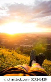 Male feet in flip-flops relaxing on green grass on the top of a mountain at sunset