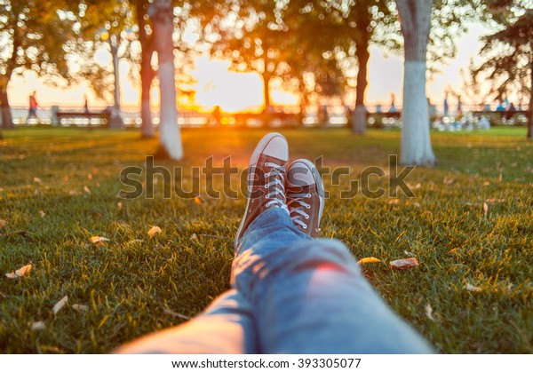 Male feet in gumshoes on green grass in the park at sunset