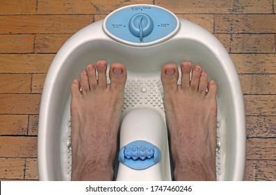 Pies masculinos dentro de la bañera de plástico para pedicura listos para el tratamiento