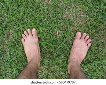 Male feet on area of grass in Thailand.