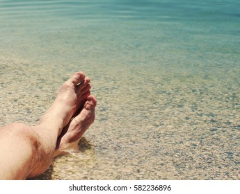 Male feet on a beach against the sea in a summer sunny day. Vacation at the sea