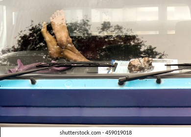 Male feet on the dashboard of the truck. Lorry driver resting in the cabin. Feet behind the windscreen of the car.