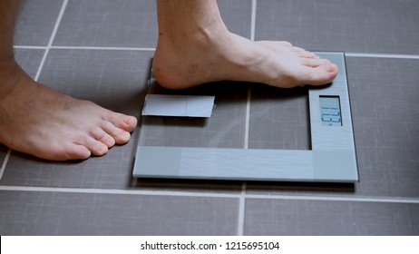 Male feet on glass scales, men's diet, body weight, close up, man stepping up on scales, side view