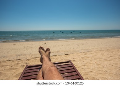 Male feet on lounge first person view from bungalow on the sea with sand beach. Men's legs on the chair from the first person view of the sea with a sandy beach