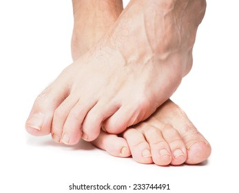 Male feet one over the other isolated towards white
