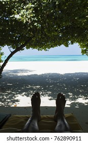 Male feet in the shade of a tropical paradise, relaxing looking out to the clear blue sea