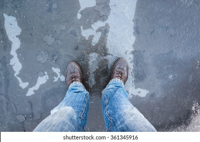 Male feet standing on frozen puddle with thin ice and falling leaves