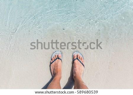 70efa650d433c Male feet wearing female flip flops at beach. Funny image of a man at  seaside