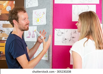 Male and female 3D designers discussing over charts in printing studio