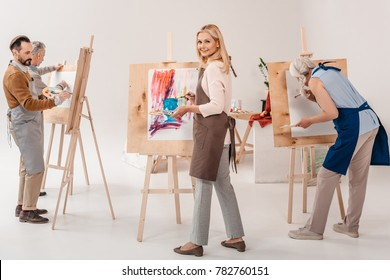 male and female adult students in aprons painting together on easels in art class