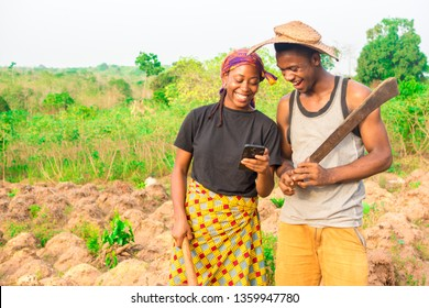 male and female African farmers on a farm smiling while viewing something on a phone together