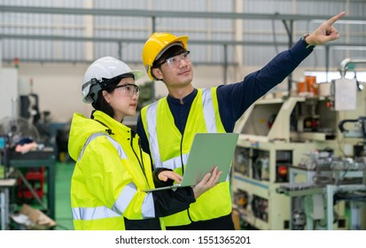 Male and Female asian Industrial Engineers Look at Laptop and Discusses Project Details in the Heavy Industry Manufacturing Factory with Various Metalworking Processes.