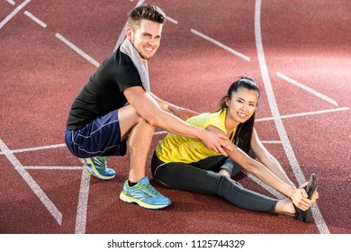 Male and female athlete doing stretching exercise together as preparation for short distance run