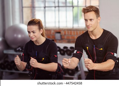 Male and female athlete wearing ems workout top and strapped to heart monitors