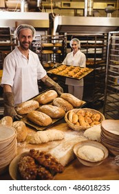 Male and female baker holding tray of loaf and michetta in bakery shop