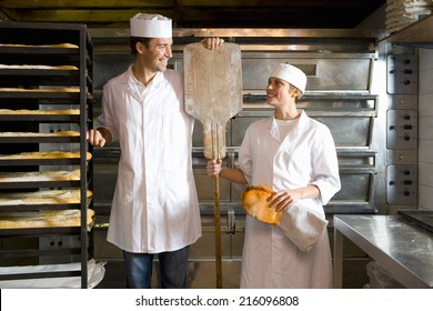 Male and female bakers smiling at each other