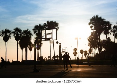 male and female basketball players at sunset in venice beach. two friends playing basketball in venice beach los angeles california