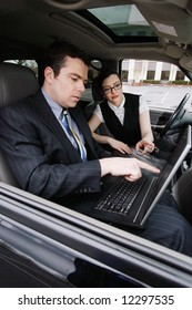Male and female business colleagues working on a laptop while sitting in a car