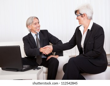 Male and female business partners laughing as they sit close together working on a laptop