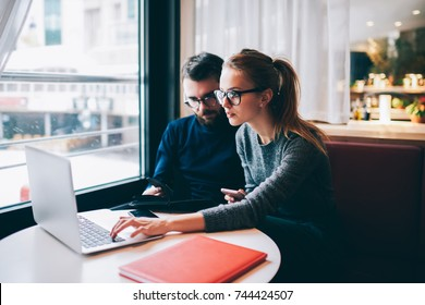 Male and female business partners in optical eyeglasses collaborating on new startup project on modern laptop computer connecting to wireless internet and using literature books for productive work