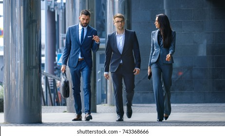 Male and Female Business People Walk and Discuss Business. They're all Working in Central Business District.