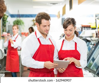 Male and female butchers using digital tablet at store with colleagues working in background