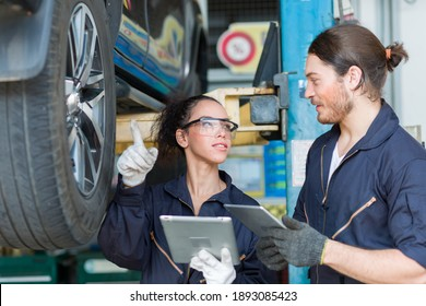 Male and female car mechanic worker checking, repair and maintenance wheel at auto repair shop. Group of  mechanic vehicle service maintenance examining wheel tire at garage. Auto car repair service