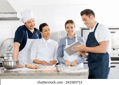 Male and female chefs checking recipe on tablet computer while preparing pasta in commercial kitchen