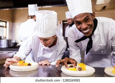 Male and female chefs garnishing delicious desserts in a plate at hotel
