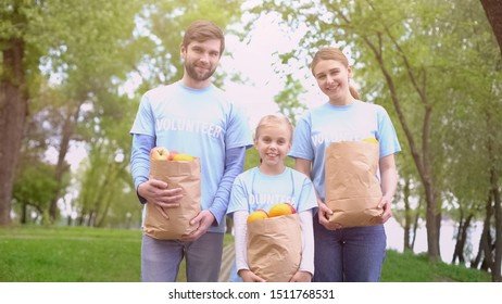 Male female and child volunteers holding paper bags with fruits, smiling camera