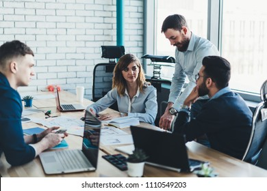 Male and female colleagues discussing working strategy of cooperation having briefing meeting in office.Team of employees in formal wear collaborating with each other sitting at table with laptops