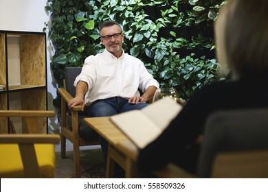 Male and female colleagues having business conversation about future collaboration between companies while sitting in modern design interior cafe discussing opinions and ideas in friendly atmosphere