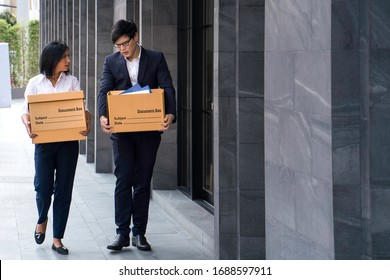 Male and female company employees are carrying their box out of the office because the company is closed or waste. Unemployed man, The economic downturn made people unemployed.