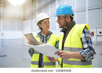 Male and female concstruction coworkers in warehouse