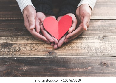 Male and female couple have a red heart on the wood table