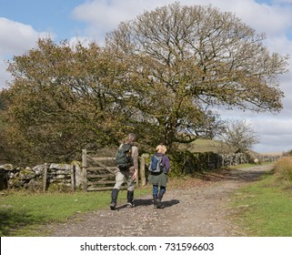 Male and Female Couple Walking in the West Dart River Valley Towards the Ancient Oak Woodland of Wistman's Wood within Dartmoor National Park in Rural Devon, England, UK