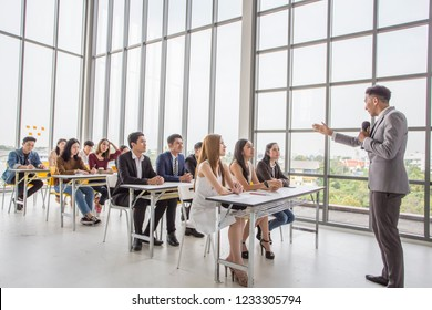 Male and female creative coworker listening explanation of male training manager speaker during workshop sitting in office.Skilled couch conducting business seminar with professionals.