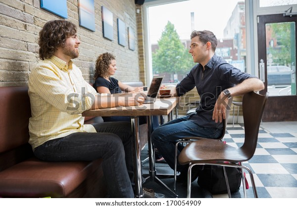 Male and female customers spending leisure time in cafe