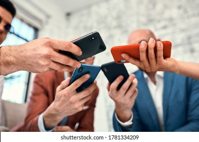 Male and female diverse hands holding cell phones, multiracial business people using smartphones applications software, users and devices concept, mobile communication